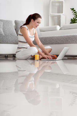 lap of luxury: The Young Beautiful Woman Sitting on the Floor with the Laptop and a Glass of Orange Juice In The Luxury Apartment
