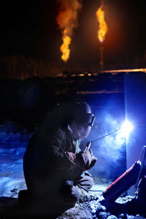 flare stack: Arc Welder working on the Oil Field