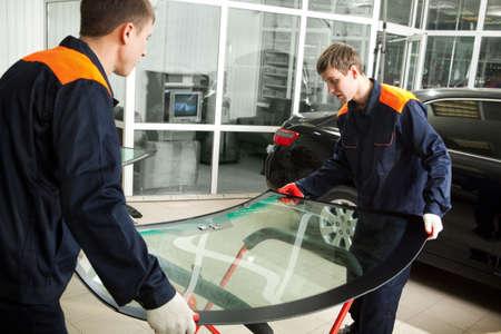 mechanic: Dos mecánicos reales que cambian el parabrisas roto del coche negro en el Garaje de reparación Foto de archivo