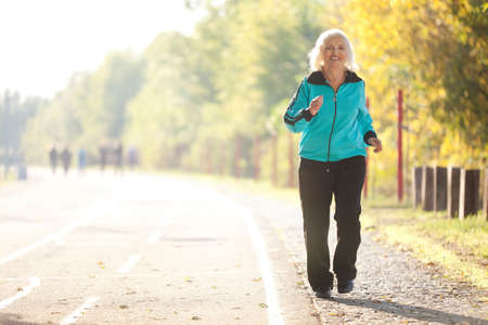 70 years old Senior Woman Jogging at the Pedestrian Walkway in the Bright Autumn Evening Stockfoto
