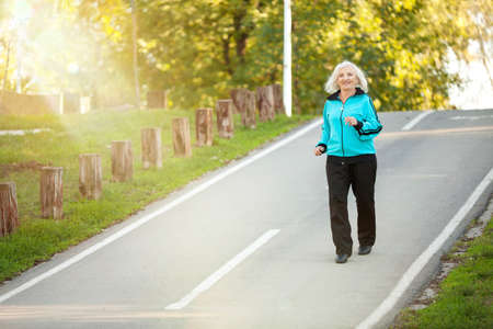 pedestrian walkway: 70 years old Senior Woman Jogging at the Pedestrian Walkway in the Bright Autumn Evening Stock Photo