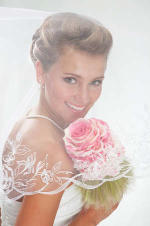 Beautiful smiling bride in the veil with bouquet at the gray background photo