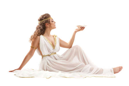 The Beautiful Young Woman Sitting on the Floor, Holding the Gold Bowl with Nectar and Wearing White and Gold Greek Costume on the White Background 스톡 콘텐츠