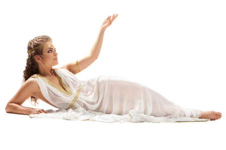 tunic: The Beautiful Young Woman Sitting on the Floor Wearing White and Gold Greek Costume, Raising Her Arm on the White Background