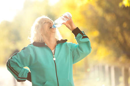 Senior Woman Drinking Water after Jogging Outdoors in the Bright Autumn Evening Stock Photo