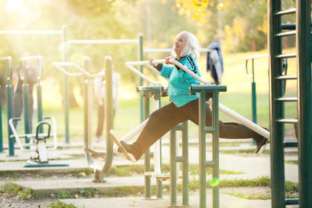 Woman doing Exercises for Legs Outdoors in the Bright Autumn Evening Stock Photo