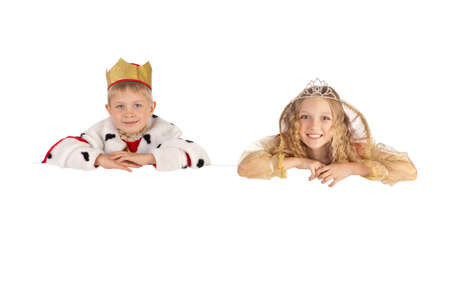 Cute smiling boy and girl in the king and queen costumes holding the sign
