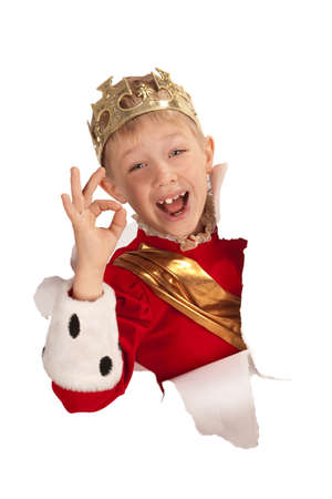 Laughing little kid wearing a crown with hand sign Ok looking out from the paper