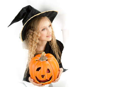 little beautiful witch with Jack O Lantern peeking through a hole in white paper Stock Photo