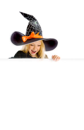 Beautiful surprised little girl with long blonde hair in the witch costume looking down the sign. Black witch hat with web, spider and orange bow. Copy space. Stock Photo