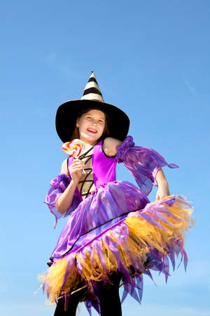 Cute Emotional Little Girl in a Costume of Witch Licking a Colorful Candy at the Blue Sky.