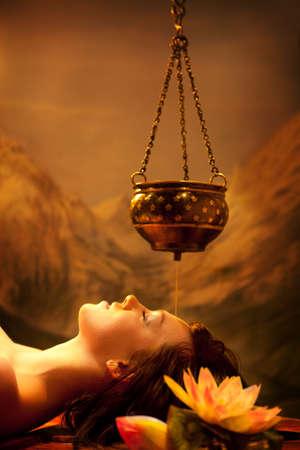 Salon de spa: Belle jeune femme ayant Shirodhara - Massage à l'huile d'Ayurveda en Inde Spa Salon avec Lotus Banque d'images - 90708704