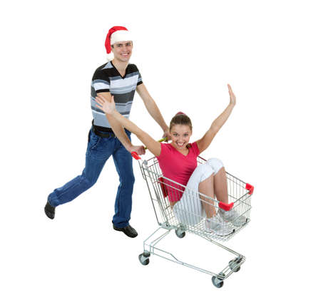 Young Woman Rides in a Shopping Basket, Led by a Young Man in Santa Hat on White Background