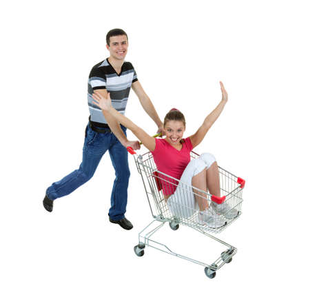 Young Woman Rides in a Shopping Basket, Led by a Young Man on White Background