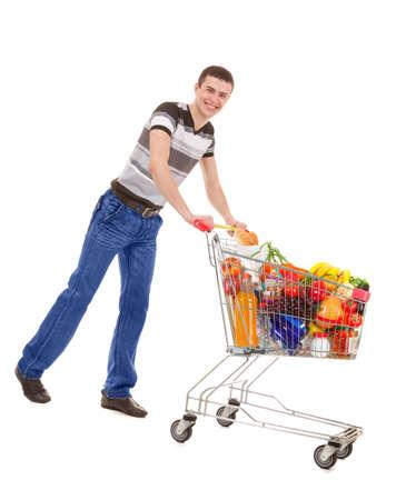 Hombre joven que sostiene una carretilla llena de las compras con las compras de productos diarios aislados en el fondo blanco Foto de archivo - 90660767