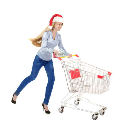 Young Woman Running with Empty Shopping Trolley for Christmas Purchase in Santa Hat  and a Big Bundle of Dollars isolated on White Background