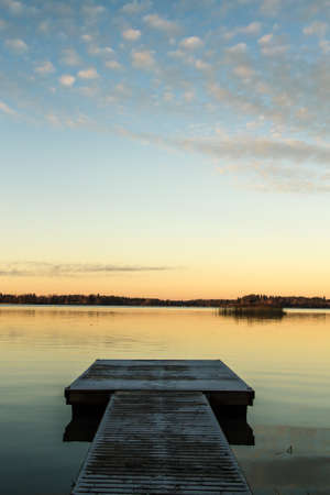 Scandinavian lake in the sunset with jetty photo
