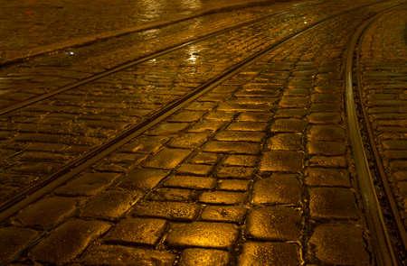 Shiny wet cobblestones with tram rails in the rain photo
