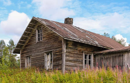 Abandoned old log farmhouse against the blue skies photo