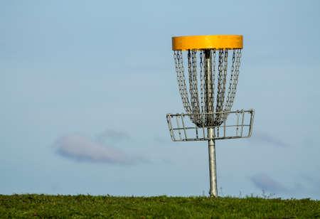 disc golf: Frisbee golf basket against blue sky on the green grass
