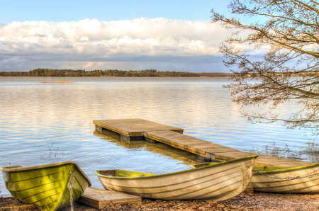 Rowboats and a pier by the lake under the low clouds photo