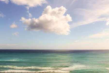White clouds over surfers in the Pacific Ocean in Waikiki Beach in Honolulu, Hawaii photo