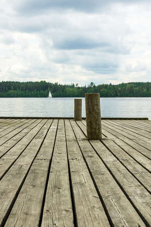 docking: Docking poles on the old wooden pier with a lake and forest background