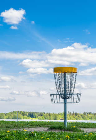 disc golf: Frisbee golf basket on the grass against beautiful cloudy sky
