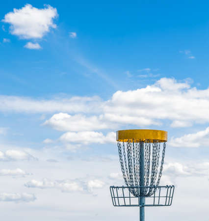disc golf: flying disc golf basket on the grass against beautiful cloudy sky and a blurry forest on the background