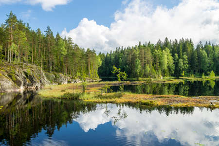White summer clouds reflecting on the forest pond in Nuuksio National Park in Southern Finland Reklamní fotografie