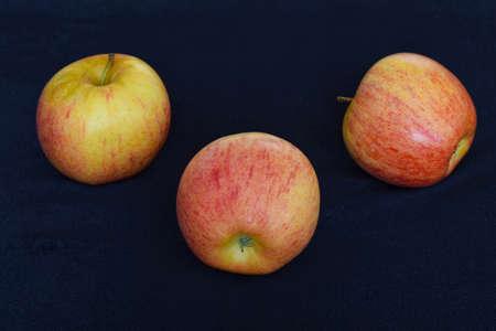 three apple on dark background