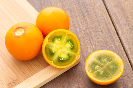 Fruits and slices of lulo or naranjilla on the wooden table - Solanum quitoense