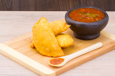Colombian empanada with spicy sauce on wooden background, typical food of Colombia