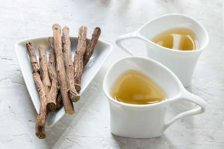 Licorice tea and roots on white background Stock Photo