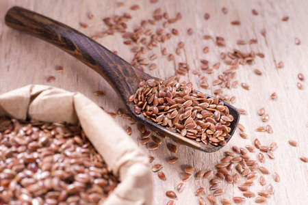 linseed seeds in container and spoon on the table.
