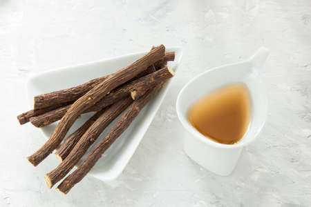 Licorice tea and roots on white background Banque d'images