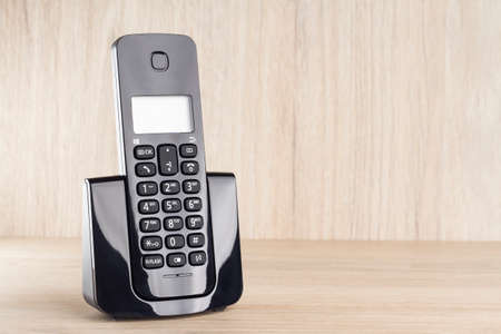 wireless telephone on wooden background.
