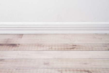 wooden floor and plaster skirting board.