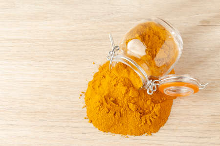 turmeric powder in glass bowl on wood- curcuma longa
