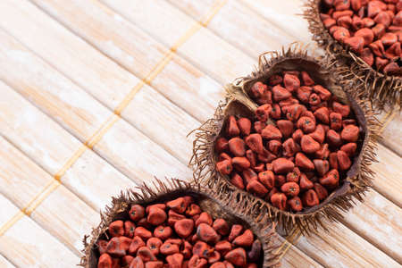 Annatto seeds on rustic wood, top view