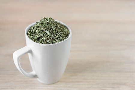 white cup with moringa leaves on wooden background Standard-Bild
