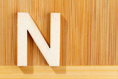 Letter N of wood-made alphabet, top view and space for text