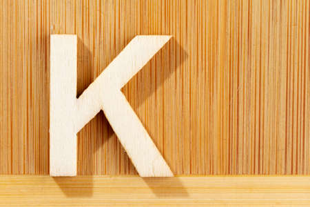 Letter K of wood-made alphabet, top view and space for text Stok Fotoğraf