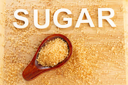 Pile of cane sugar on wooden background, word sugar