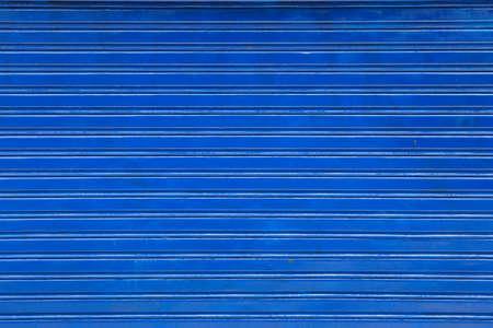 blaue Rolltür aus Metall, horizontal gestreifter Hintergrund Standard-Bild