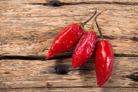 three red chili peppers on rustic wooden background
