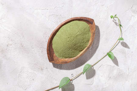 Moringa powder in wooden bowl on white background (Moringa oleifera)