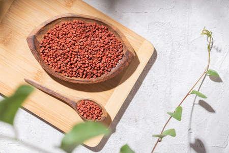 achiote grains in wooden bowl on white background (Bixa orellana)