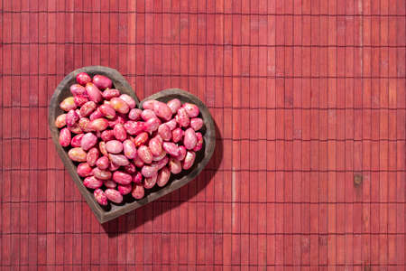 Red kidney beans in heart bowl on red wood