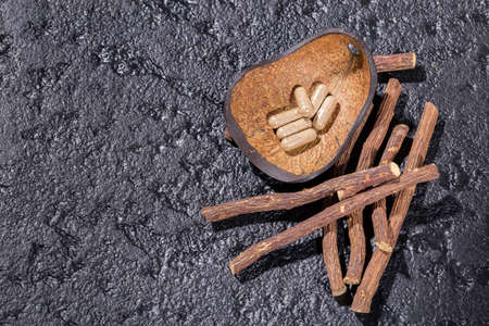 licorice root and tablets on black background